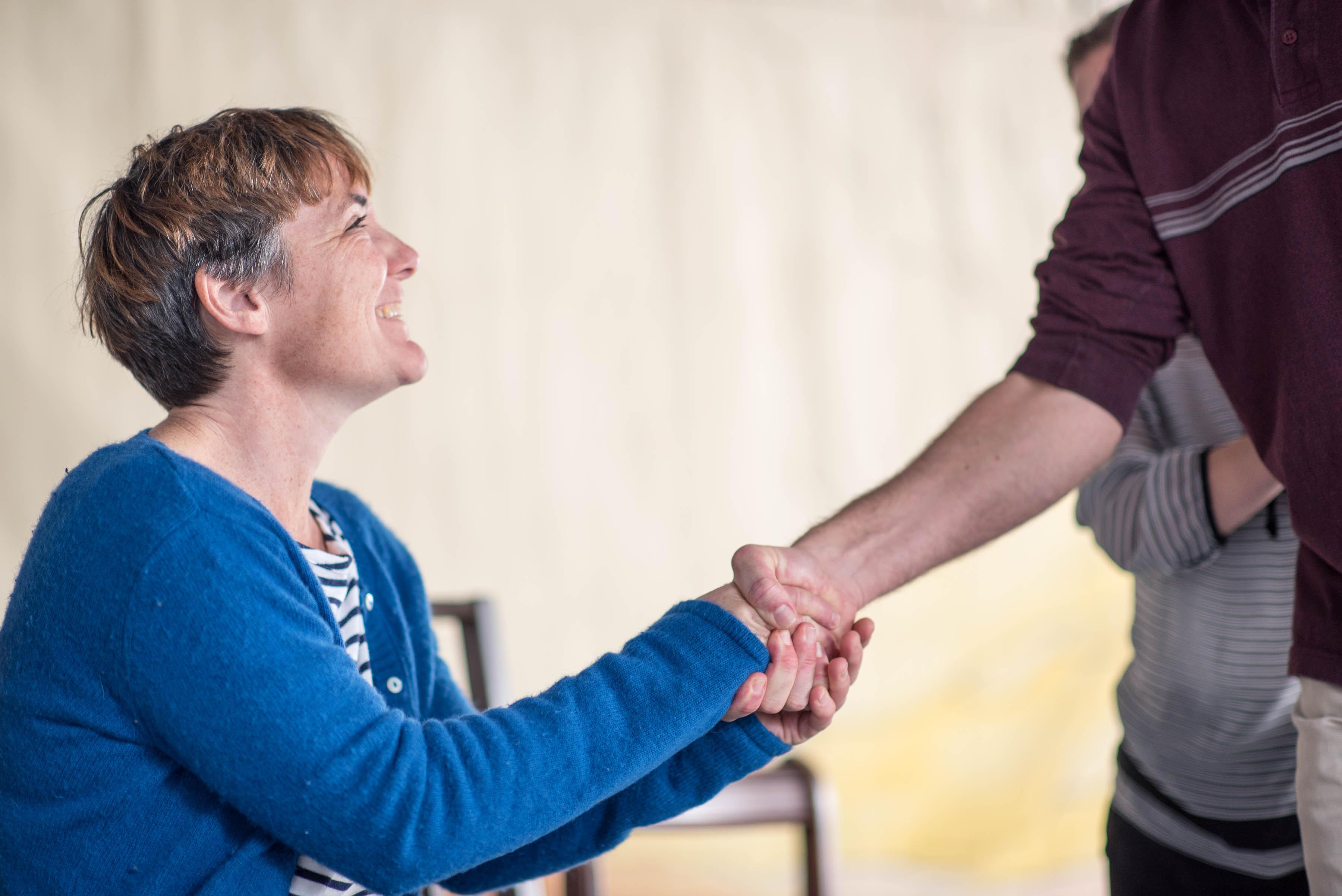 actors shaking hands - support
