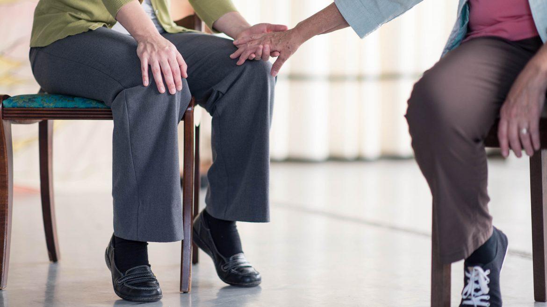 actors touching hands just shot of knees - Cracked on Dementia